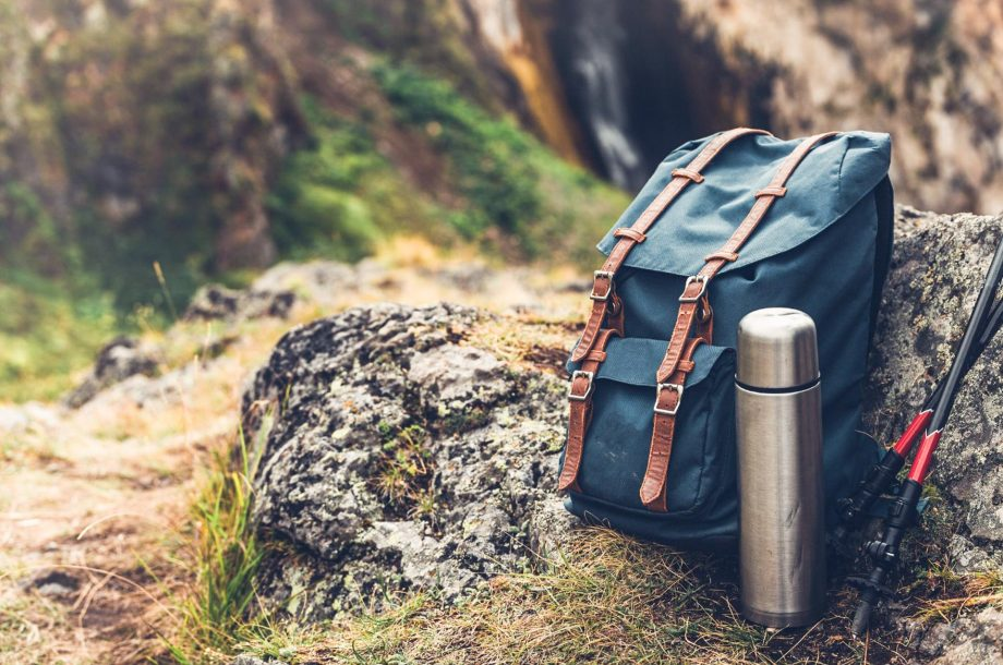 Hipster Blue Backpack, Thermos And Trekking Poles Closeup, Front View. Tourist Traveler Bag On Rocks Background. Adventure Hiking Outdoor Concept (Hipster Blue Backpack, Thermos And Trekking Poles Closeup, Front View. Tourist Traveler Bag On Rocks Bac